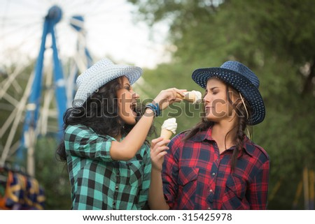 two beautiful girls in cowboy hats eating ice cream