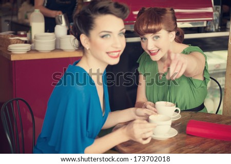 Two beautiful girls in retro style in retro cafe
