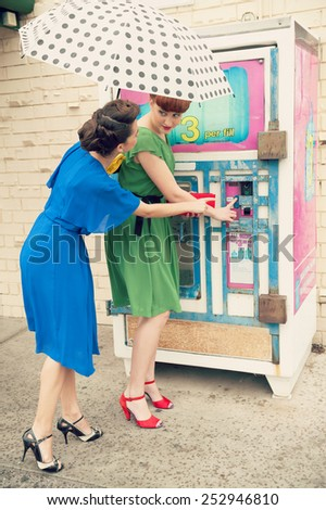 Two beautiful girls in retro style near a water machine - stock photo