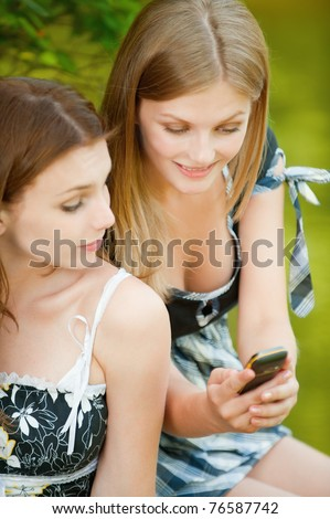 Two beautiful girls in summer city park and read sms on mobile phone.