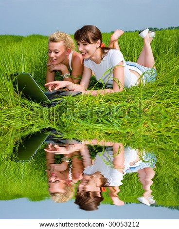 Two beautiful girls in white clothes are laughing and looking at laptop computer outdoors. Lay on the green grass. - stock photo