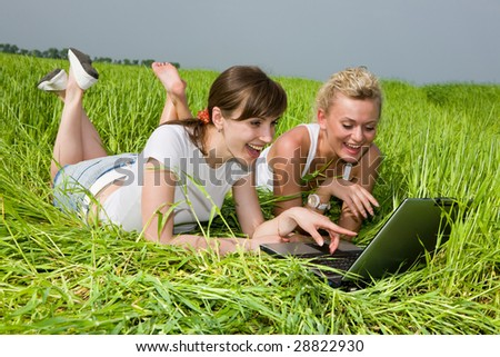 Two beautiful girls in white clothes are laughing near laptop computer outdoors. Lay on the green grass - stock photo