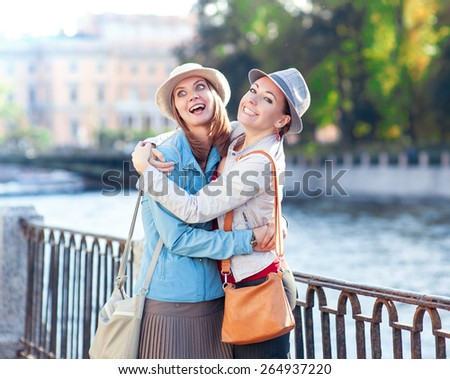 Two beautiful girls laughing and hug in the city outdoor - stock photo