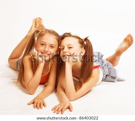 Two beautiful girls  laying on white - stock photo
