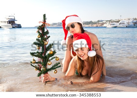 Two beautiful girls lie on the beach with a Christmas tree