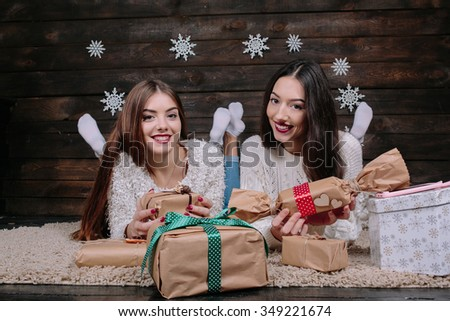 Two beautiful girls lie on the floor between the gifts for Christmas - stock photo
