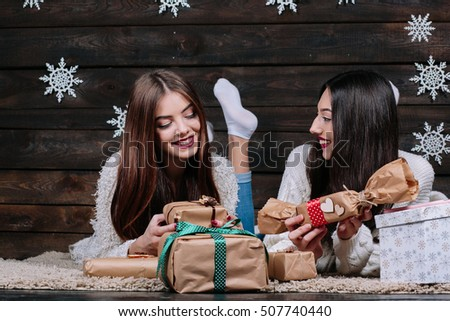 Two beautiful girls lie on the floor between the gifts for Christmas