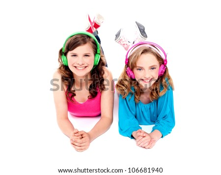 Two beautiful girls lying on floor wearing headphones and enjoying music - stock photo