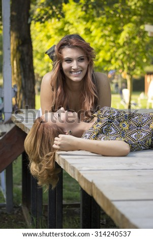 Two beautiful girls lying on wooden boards.