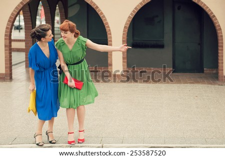 Two beautiful girls on the street in retro style.Urban scene with young women