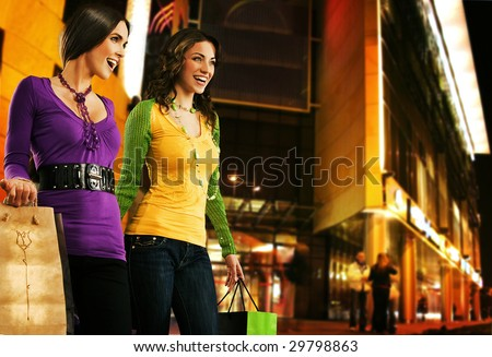 Two beautiful girls over shopping center at the evening - stock photo