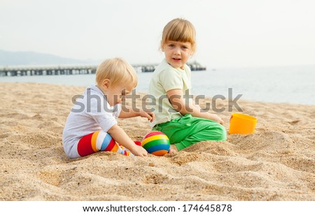 Two beautiful girls play on the beach