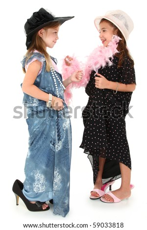 Two beautiful girls playing dress up in baggy dresses and hats over white. - stock photo