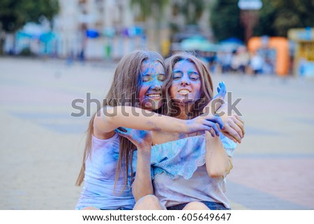 Two beautiful girls playing with colored paints dry in summer city