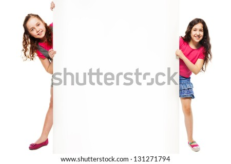 Two beautiful girls showing blank white poster for advertising to be inserted, standing isolated on white - stock photo
