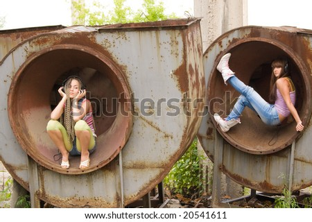 two beautiful girls sit in circles and listening music - stock photo