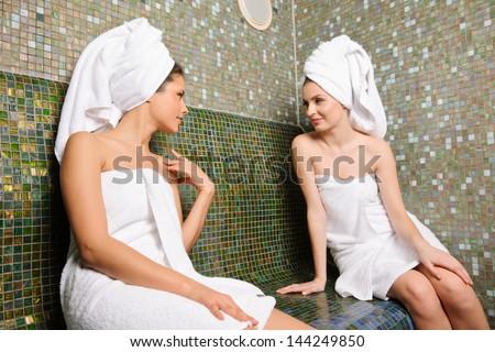 Two beautiful girls talking in Turkish sauna - stock photo
