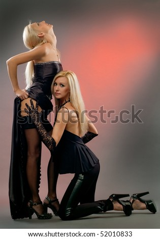 Two beautiful girls to models in evening cloth pose on gray background