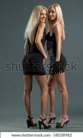 Two beautiful girls to models in evening gowns pose on gray background