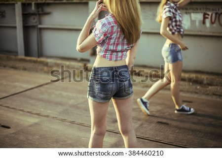 Two beautiful girls walking on metal bridge and dancing. Friends wearing stylish shirt and jeans shorts , enjoying day off and have fun. - stock photo