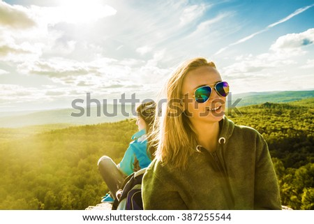 two Beautiful girls wear sunglasses on the rocks Young adult women sit on pick mountain against blue sky with clouds and forest trees background Empty space for inscription Sun light rays - stock photo