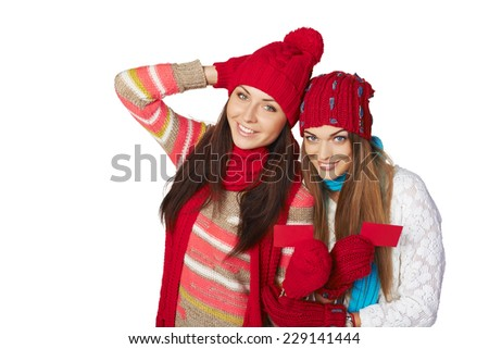 Two beautiful girls wearing winter hats, mufflers and gloves showing blank red cards - stock photo