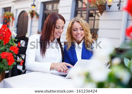 Two beautiful girls with laptop in summer cafe