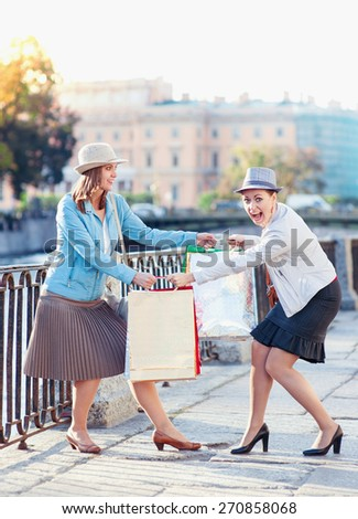 Two beautiful girls with shopping bags having fight in the city outdoor - stock photo