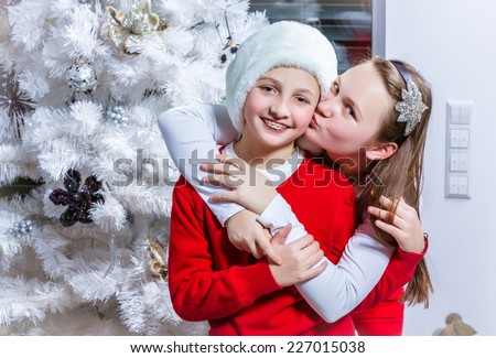 two beautiful happy child at the Christmas tree - stock photo