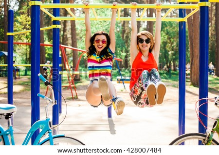 Two beautiful happy funny hipster girls, best friends, hang on the crossbar on the horizontal bar on the playground, laughing, play the fool, fun watching, a great sunny summer day, Lifestyle - stock photo