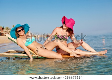 Two beautiful happy girls in bikinis and colorful hats resting on the beach a summer day
