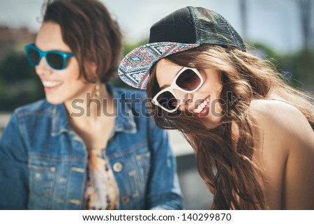 Two beautiful happy girls in sunglasses on the urban background. Young active people. Outdoors - stock photo