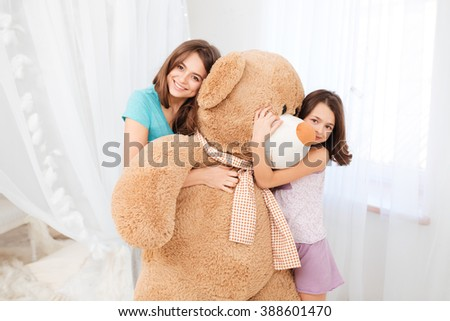 Two beautiful happy girls standing and embracing huge plush bear in children room - stock photo