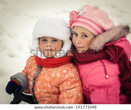 Two beautiful happy sisters winter outdoors. - stock photo