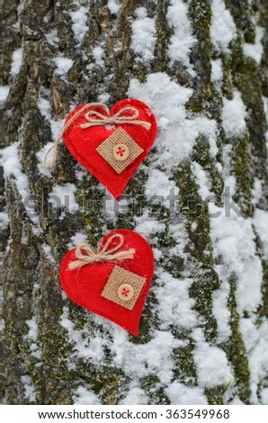Two beautiful hearts are on a snowy tree trunk. Concept of love and St. Valentines Day. - stock photo