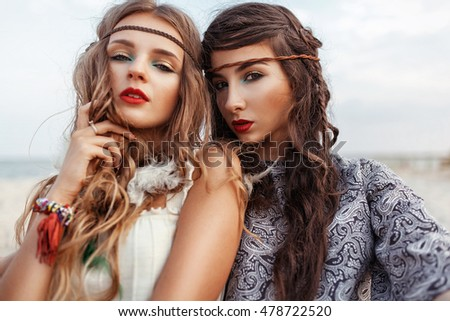 Two beautiful hippie girls with dright make up and hairstyle looking at camera
