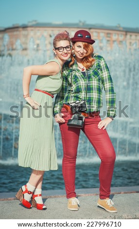 Two beautiful hipster girls with retro camera  - stock photo