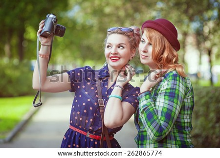 Two beautiful hipster girls with retro camera outdoor - stock photo
