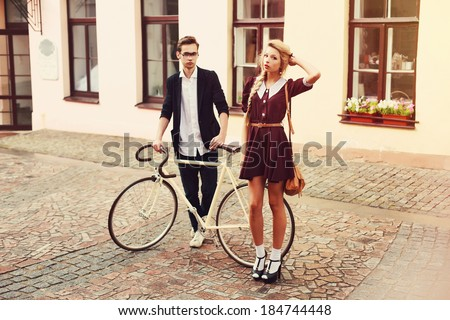 Two beautiful hipsters standing outdoor on the street in summer with white vintage fixed gear bicycle. Pretty blonde woman in short dress having fun in europe - stock photo
