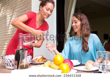 Two beautiful hispanic women enjoying an outdoor home meal together, one pouring water into a glass. - stock photo