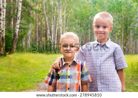 Two beautiful joyful smiling happy blond children (little boys, brothers) outdoor having fun in summer park. Togetherness and friendship, close up portrait. - stock photo