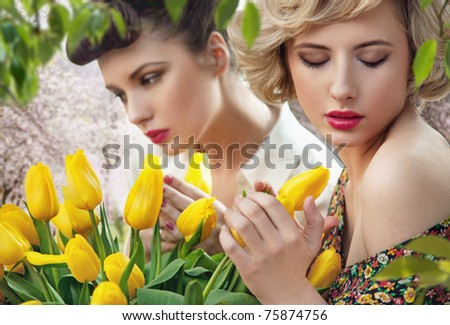 Two beautiful ladies in a tulip garden - stock photo