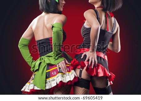 Two beautiful ladys in cool costumes from the back - stock photo
