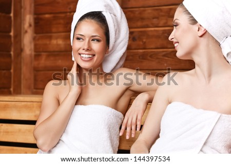 Two beautiful laughing females sitting and talking in sauna - stock photo