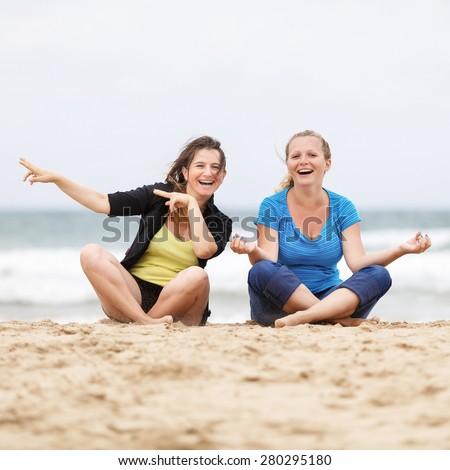 Two beautiful laughing young women have fun and enjoy sitting on the sand at the beach. Shallow depth of field. Focus on the models. - stock photo