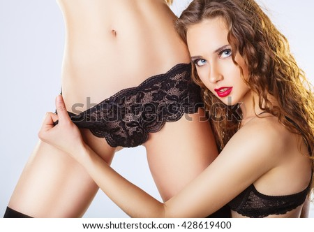 Two beautiful lesbian women in erotic foreplay game on a white background. Sexy woman pulling black panties - stock photo