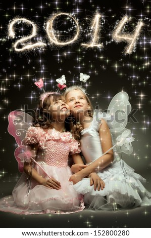 two beautiful  little girl with wings, sit and  smile on dark background, 2014 Christmas concept - stock photo