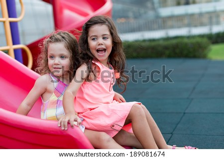 Two beautiful little girls having fun on the playground - stock photo