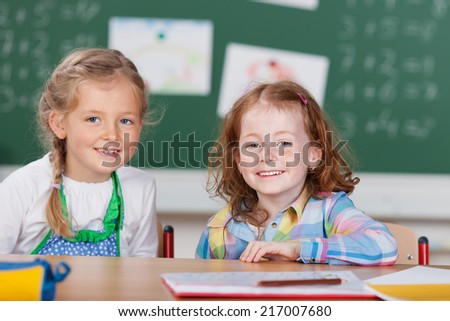 Two beautiful little girls in kindergarten sitting side by side at their desk in the classroom smiling happily at the camera - stock photo