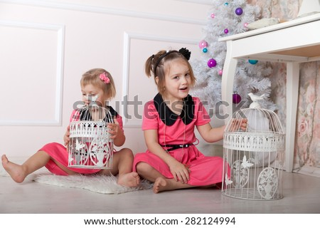 Two beautiful little girls sitting on   floor with   bird cages.